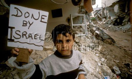 A young boy stands outside his family's destroyed home with a homemade sign blaming Israel for the damage. The IDF bulldozed the center of the camp after fierce fighting leaving many dead.