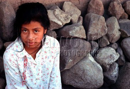 A pretty, young girl stares into the camera lens in San Salvador, El Salvador, Central America.