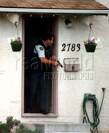 A member of the RCMP cautiously searches a house for a lone gunman in Kelowna, British Columbia, Canada.