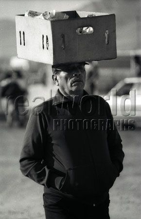 A Mexican man balances a box on his head while keeping his hands warm in Chihuahua, Mexico. G