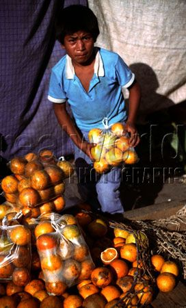 A young boy sells bags of oranges at a market in the jungle town of Leticia, Colombia, South America.